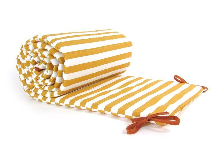 Protector de cuna con estampado de rayas color miel.