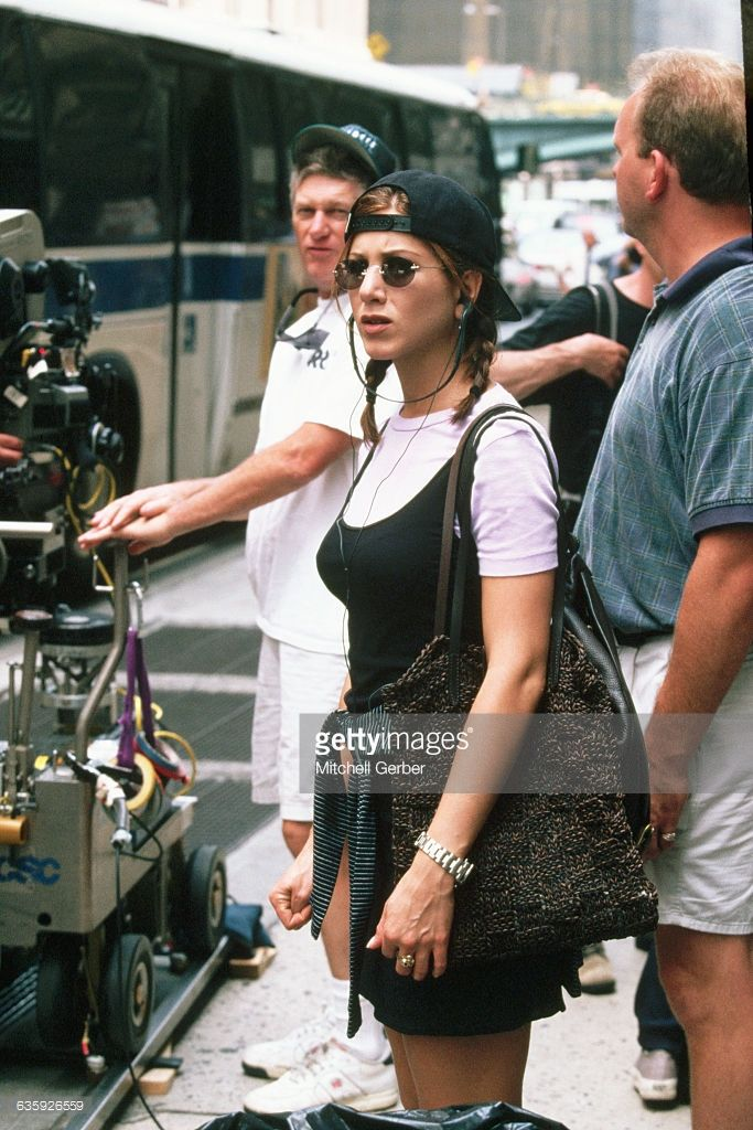 Wearing a backwards baseball cap and sunglasses, actress Jennifer Aniston stands on the set of the motion picture, Picture Perfect, during filming on the streets of New York City.