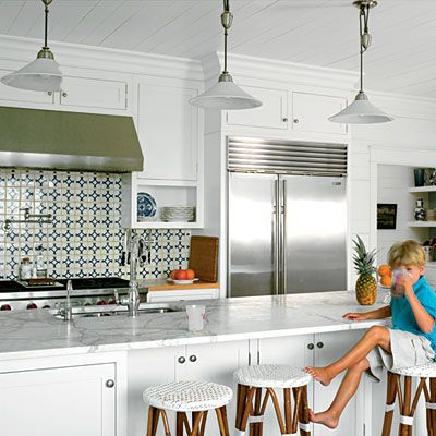 A colorful tile backsplash and beachy barstools brighten up the kitchen. White walls, cabinetry, and countertops open up the space and give it a clean yet modern feel.