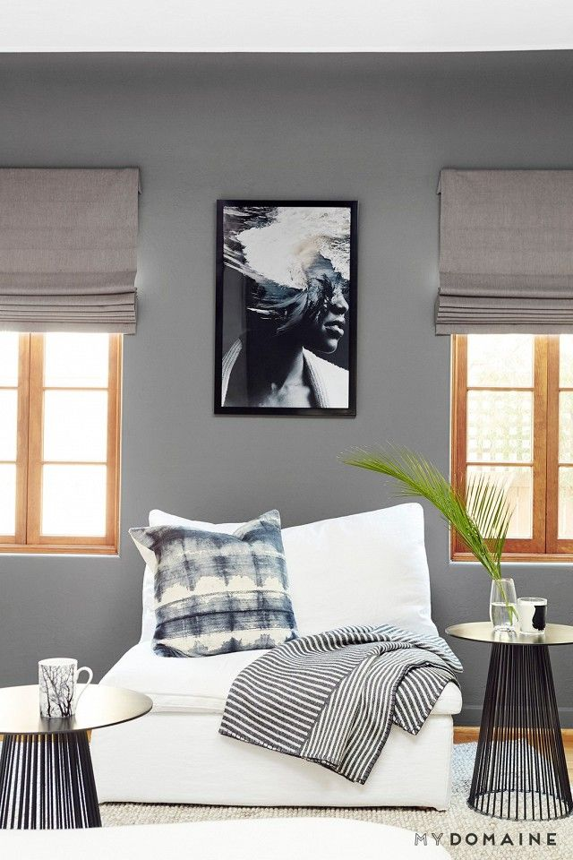 Living room with a white linen armchair, modern metal tables, and modern black and white art