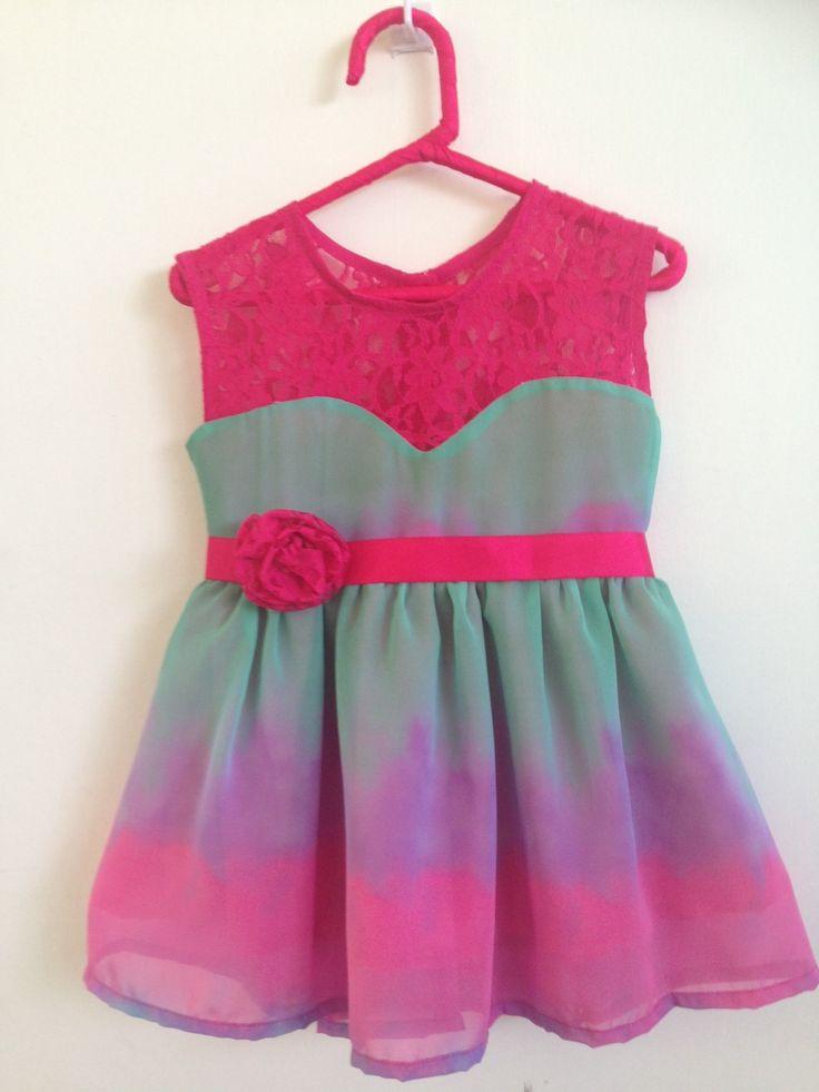 Vestido en chifón multicolor con randa fucsia y detalle en la cintura.  El prendedor de flor se lo puede usar en el cabello.  Talla 3-4 años.