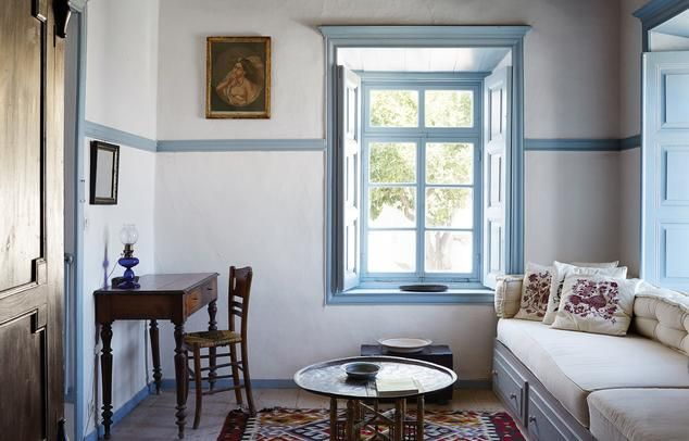<strong>SITTING PRETTY</strong> | The ground-floor sitting room of Forno Annex, featuring a portrait from a salon in Patmos on the wall and a cobalt blue oil lamp on the writing desk.