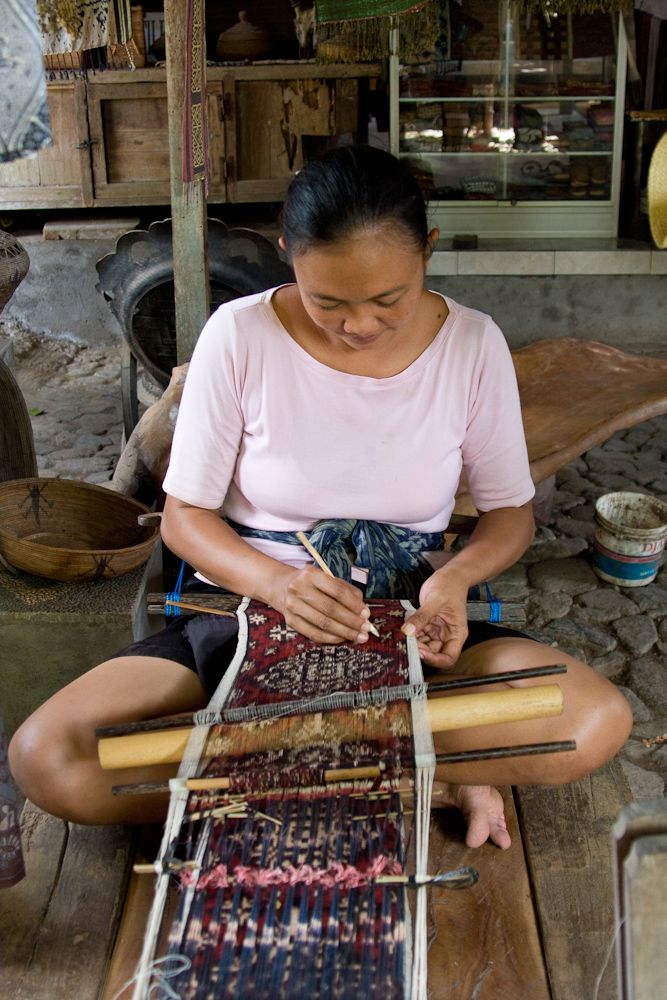 Weaver working on a double ikat using a traditional loom in Tenganan, Bali.