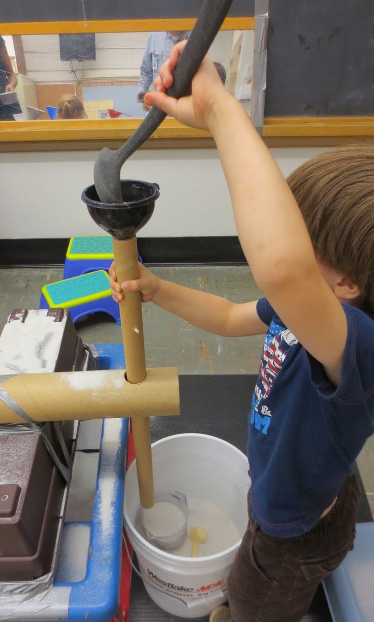 Filling a cup by spooning sand into the tube through the funnel ≈≈