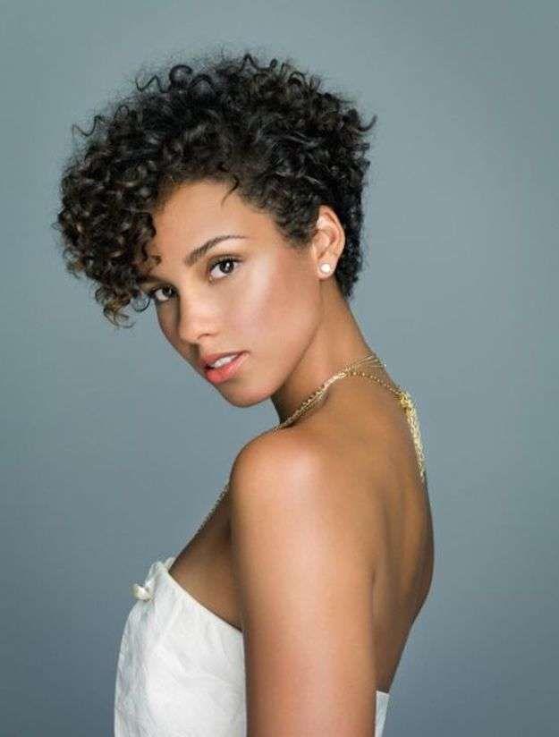 Alicia Keys con el pelo corto rizado - Alicia Keys con el pelo rizado con corte corto y todo peinado hacia arriba y con volumen. Lleva un maquillaje con tonos brillantes.  Fuente: Pinterest