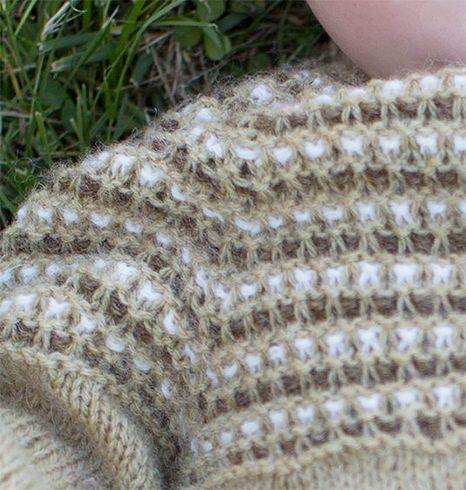 En tynn heldress til baby og barn i slitesterkt og melert garn i ren ull; dette er en dress som kan brukes hele året. Vevstriken på bærestykket pynter opp.