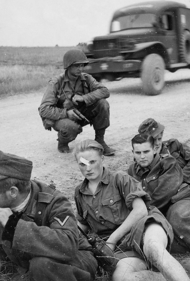US soldier guarding captured German soldiers during World War II.