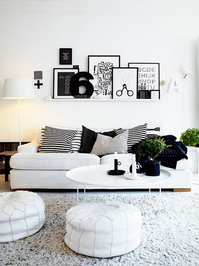 Black & whites prints over a white couch covered in black & white striped pillows