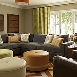 living rooms - gray walls blue modern sectional sofa orange zigzag chevron rug white orange leather round tufted ottomans brown leather chair orange linen drum pendants Kelly Wearstler Imperial Trellis Fabric - Citrine