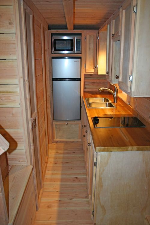 The kitchen has a butcher block counter, upper cabinets, an electric cooktop, and space for a small refrigerator and microwave.