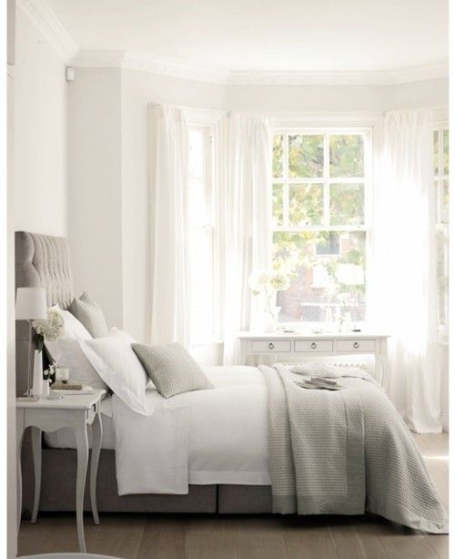 Pretty gray and white bedroom.  Love the Button tufted gray headboard and the wall of windows, which let in so much light.