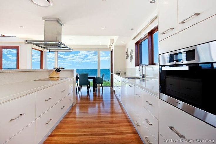 A modern white kitchen with a breathtaking lakefront view!