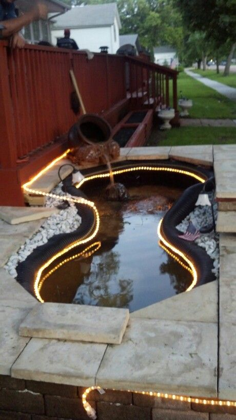 Up-cycled Koi pond.   Two loader tires, pond liner, drain tile, paver wall with Travertine tile top.