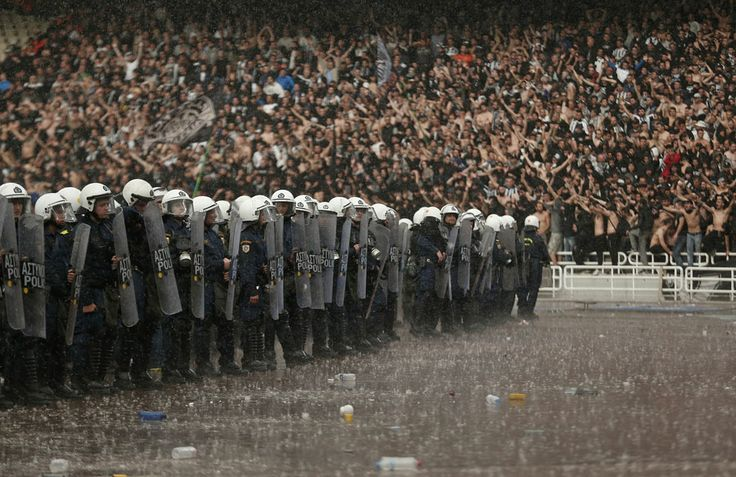 Policemen stand guard under heavy rain in front of PAOK Salonika fans before their Greek Cup soccer final against Panathinaikos at the Olympic stadium in Athens, April 26, 2014. REUTERS/Yorgos Karahali