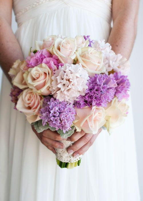 Hand held vintage style bouquet, featuring ice pink, creamy pink, lavender and lilac tones. Florals include hyacinth, roses, sweet pea and dusty miller. Finished with antique style lace feature.