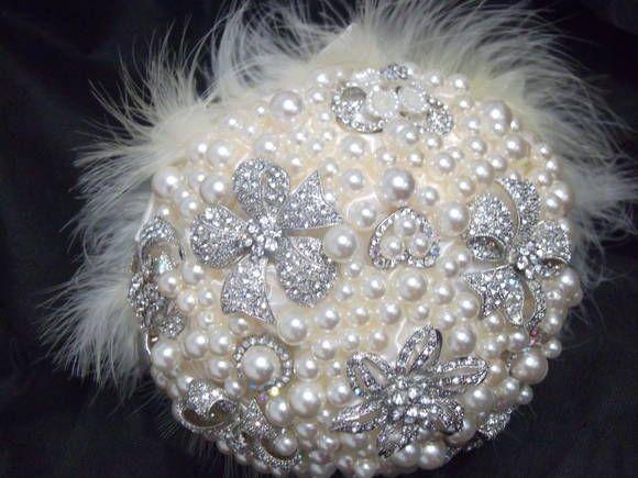 Buquê de pérolas com broches, plumas e cetim. Pedidos com mínimo de antecedência de 30 dias da data do casamento.