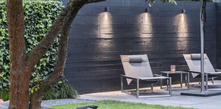 Svart plank, breda brädor, belysning, murgröna, flerstammigt träd med sittlåda runt, grusgång.
