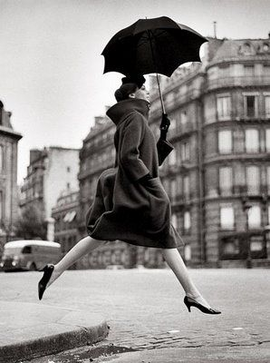 Henri Cartier Bresson woman with umbrella (and dangerously-heeled shoes to make that leap!)