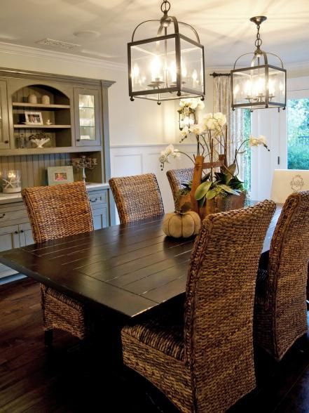 The rattan furniture in this neutral dining room instantly transforms the space into a casual place to dine with family and friends. Two carriage lights and white orchids bring warmth to the space, and wainscoting adds texture for a beachy feel. Design by Darci Goodman