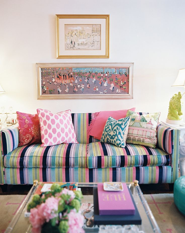 A striped couch and patterned pillows paired with a Lucite coffee table
