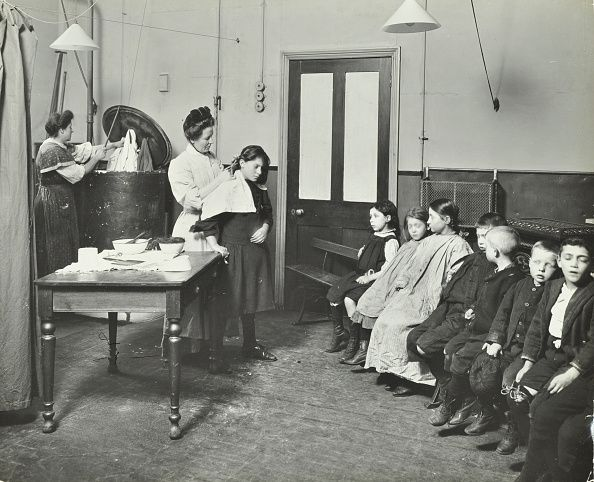 Nurse cutting children's verminous hair Finch Street Cleansing Station Stepney London 1911 A nurse treats children whose hair is infested with lice...
