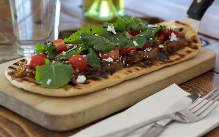 FLATBREAD A great option to share - traditional flatbread; topped with caramelized onions, Happy Valley goat feta, semi sundried tomatoes, oven baked then topped with baby kale, drizzled with balsamic reduction and olive oil. 1609 Restaurant & Lounge | Food Photos