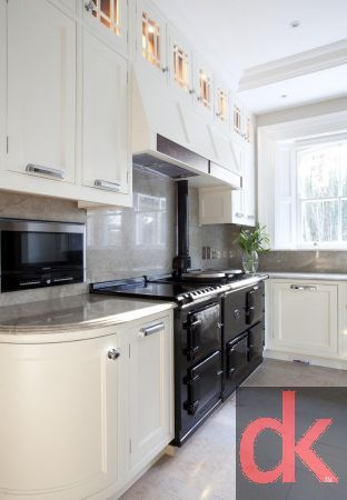 Luxury hand painted kitchen cabinetry with walnut kitchen cabinetry doors with burr walnut accents.  Curved glass kitchen doors with custom inlay.  Exotic stone worktops along with custom made dining table and chairs.  Aga cooking