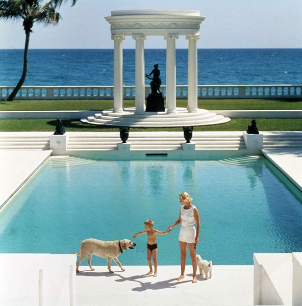 American writer C.Z. Guest (Mrs F.C. Winston Guest, 1920 - 2003) and her son Alexander Michael Douglas Dudley Guest in front of their Grecian temple pool on the ocean-front estate, Villa Artemis, Palm Beach.