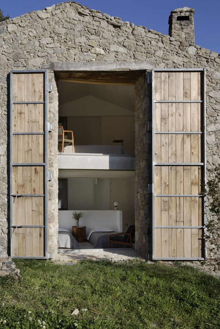 "House in Extremadura • Abaton Architects. Fantastic over-sized doors. ""Large wooden shutters that slide closed like a second skin, cover the large windows at night to trap in most of the home's daily solar heat gain."""