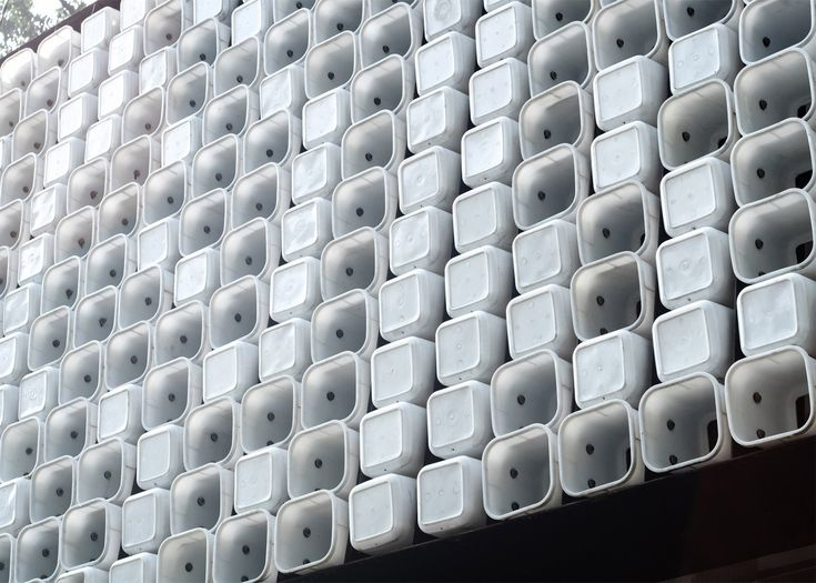 Two thousand ice-cream tubs form the walls of this small community library in Bandung, Indonesia, and some have been perforated to display a subtle message