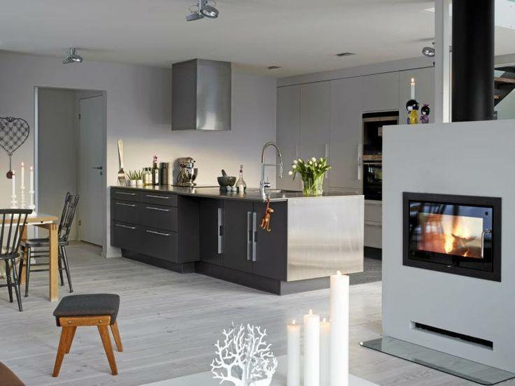 Stram stil: Kjøkkenet er integrert i spisestuen og markeres på raffinert vis med mørk innredning og polert betonggulv.Delta Light sørger for godt arbeidslys, selv nårvintermørket har lagt seg.Innredningen er tegnet av F2 interiørarkitekter og levert av Drømmekjøkken. Peisen fra Rais har vinduer på begge sider av rennkammeret, slik at du kan glede deg overflammene, uansett hvor i rommet du er.