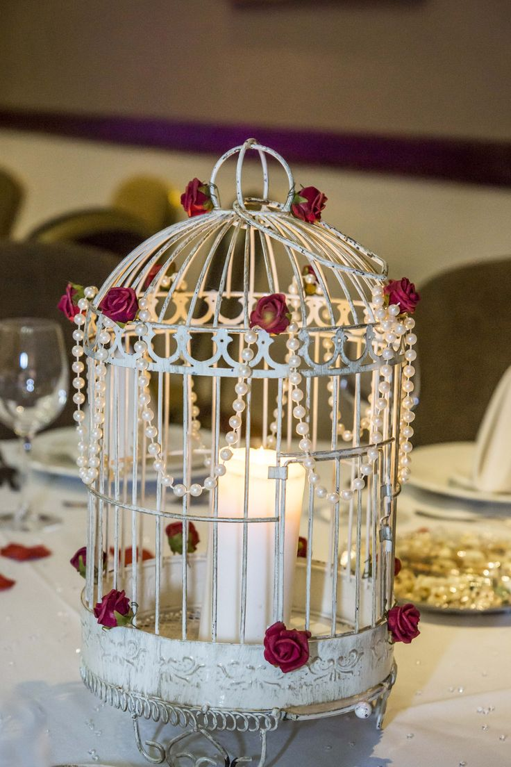 Candle in a bird cage is quite popular, you can decorate it with anything you like. Such as little red roses as seen in this picture.