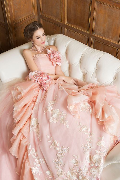 Sleeping on a white couch in a pink dress is on her bucket list. She's probably done it before, but she wants to remember it this time.