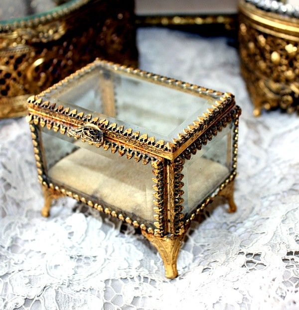 """Gilt Ormolu French style Vitrine Display Casket or Jewelry Box,     Diamond point edging, deep glass with beveled borders on the top. Inside, a velvet liner. Elegant cabriole legs, ornate scrolled design on all sides. There is wear to the gilt and glass commensurate with the age of this piece. A wonderful addition to your collection, this darling is in rectangle shape, a fabulous collectible. Measures 2-3/4"""" tall x 3-1/4"""" x 2-3/4""""."""
