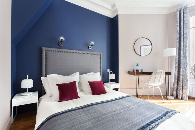 Dans cette chambre au chic parisien, deux coussins bordeaux apportent une touche chaleureuse et cosy.