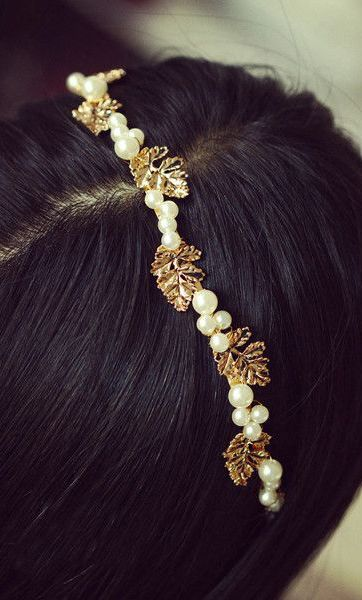 Model with black hair adorned with pearls and leaves headband