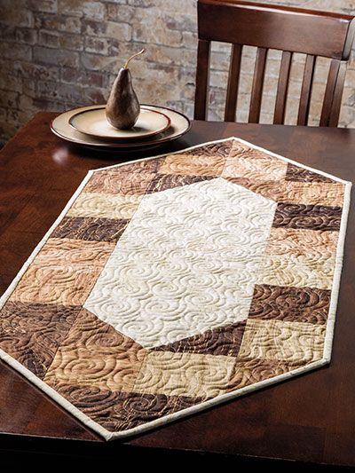 "An Exclusively Annie's Quilt Design for your table!   This table runner pattern, found only here at Annie's Craft Store, is so easy a beginner can finish it in no time! Designed by  Quilter's World  Editor Carolyn Vagts, this runner uses just 1 pack of 5"" charm squares that contains at least 24 squares, plus just a bit of coordinating fabric. Samples shown were made with Artisan Spirit Sandscapes (shown below). Finished size is 18 1/2"" x 44""."