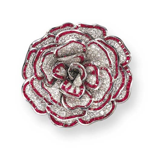 "AN EXQUISITE RUBY AND DIAMOND ""CAMELLIA"" BROOCH, BY RENÉ BOIVIN  Designed as a series of overlapping pavé-set diamond petals, further accented by calibré-cut rubies, mounted in 18K white gold and platinum, circa 1938, with French assay marks and maker's mark"