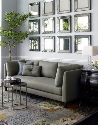 Mirrors in living room decor. Tailored contemporary sofa next to antique Bombay chest
