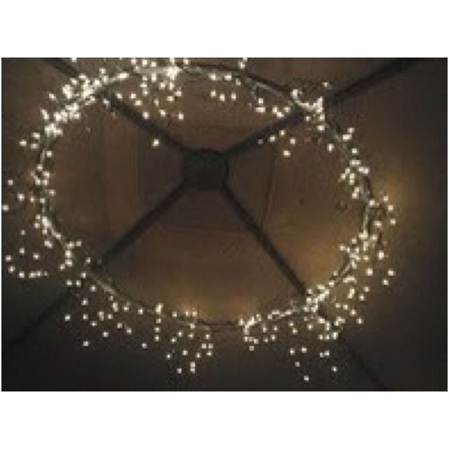 Hula hoop wrapped with Icicle lights. 1 hula hoop (spray painted) + 2 strings of icicle lights and black electrical tape = magnificent chandelier. So pretty!