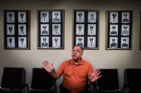 Bernie Cybulski, vice ordförande i polisfacket, sitter framför porträtten av polismännen som dött i tjänst.