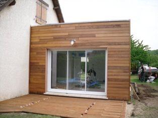 Agrandissement de maison réalisé en ossature bois avec toit plat et bardage Reed-cedar