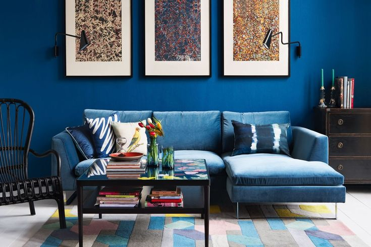 """A corner sofa, 'Jasper', covered in cotton velvet, 80 x 250 x 155cm, £2,028, from [link url=""""http://www.love-your-home.co.uk/""""]love-your-home.co.uk[/link] takes centre stage in this bright blue [link url=""""http://www.houseandgarden.co.uk/interiors/living-room""""]living room[/link].  The walls are painted in [link url=""""https://www.dulux.co.uk/en""""]Dulux[/link]'s 'Azure Fusion' paint. Wide floorboards are covered in a geometric rug and the sofa is home to a cheerful array of cushions. Our…"""