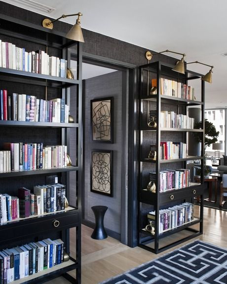 Freestanding bookshelves in a black finish with swing-arm lights above, and a dark wallpapered wall behind make a great alternative to built-ins, and keep this space a little lighter.