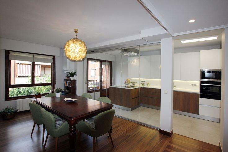 Separación con cortinas de cristal entre cocina y comedor.