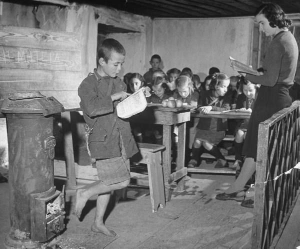 Civil War/Greece A young boy reading allowed to the class.Location:Louzesti, Greece Date taken:December 1947 Photographer:John Phillips