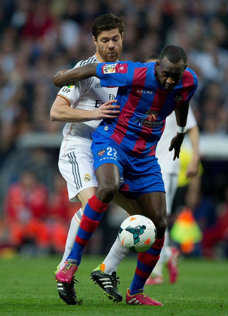 Xabi Alonso competes for the ball with Mohamed Sissoko during the La Liga match between Real Madrid CF and Levante UD at Estadio Santiago Bernabéu on March 9, 2014 in Madrid, Spain.