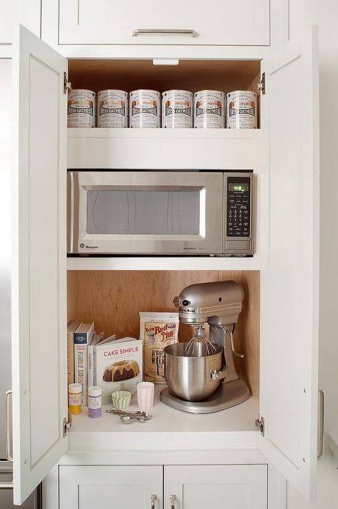 Kitchen cabinets conceals small appliances including a microwave on shelf over a KitchenAid Mixer hidden behind double doors.