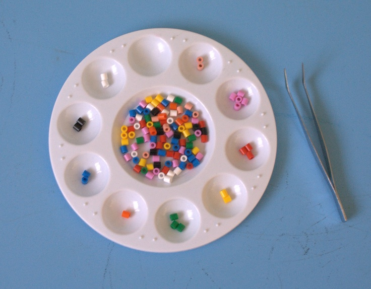 motricité fine en triant les perles de couleur à l'aide d'une pince.