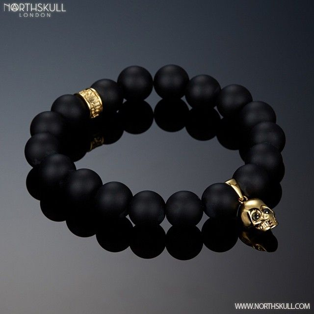 """The smooth Matte Black Onyx & 18kt. Gold Skull Charm Bracelet by @Northskull adorns the wrist perfectly. Each eye of the skull is set with a precision cut…"""